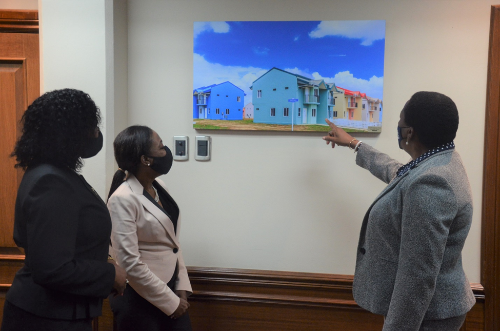 Minister Beckles looking at one of HDC's new development while PS Davidson-Williams and Ms. McFarlane look on